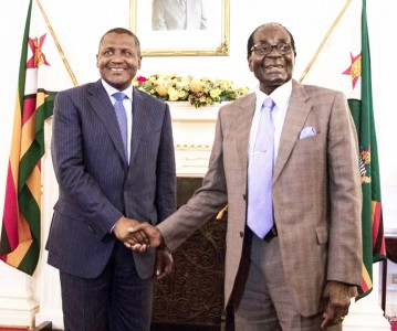 Zimbabwe's President Robert Mugabe (R) shakes hands with Africa's richest man, Nigeria's Aliko Dangote (L) prior to their meeting at State House in Harare, on August 31 2015. AFP PHOTO/JEKESAI NJIKIZANA